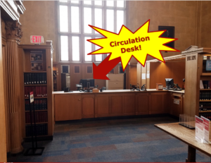 The circulation desk is located opposite the College Ave end of the Gould Reading Room.